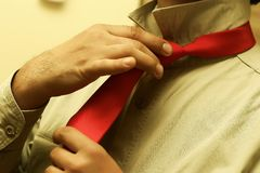 Tying a Red Tie. Man tying or untying a red tie around his neck royalty free stock image