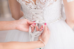 Tying ribbons on a wedding dress Stock Photography