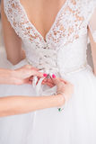 Tying ribbons on a wedding dress Stock Images