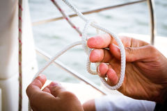 Tying a sailor knot. Sailing school: learning how to tie a knot Royalty Free Stock Photo
