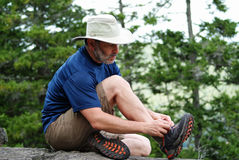 Tying a Shoelace. A man sits on a rock and ties the shoelace of his hiking boot Stock Photos