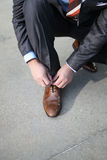 Tying shoelaces. A businessman tying his brown shoelaces Royalty Free Stock Photography