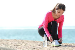 Tying shoelaces on the beach. Girl tying shoelaces while doing some exercise on the beach stock photography