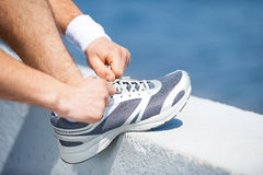 Tying shoelaces. Close-up of man tying shoelaces on sports shoe while standing outdoors stock photo