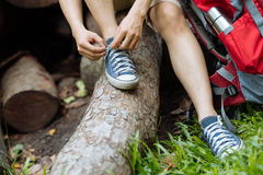 Tying shoelaces. Male hiker tying shoelaces in summer forest Royalty Free Stock Photos
