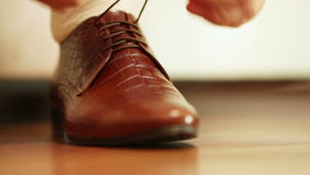 Tying shoelaces. Man tying shoelaces on expensive brown shoes stock video footage