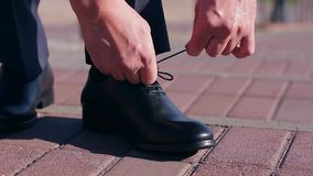Tying shoelaces. Man tying  shoelaces on leather shoes stock video footage