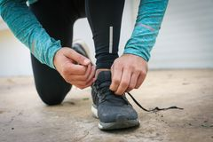 Tying shoelaces before running. Sporty man. Tying shoelaces before running. Sporty man tying sneakers on road city Royalty Free Stock Photo
