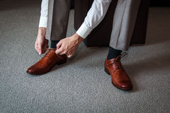 Tying shoes. A young man tying elegant shoes indoors Stock Images