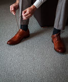 Tying shoes. A young man tying elegant shoes indoors Royalty Free Stock Photos