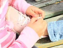 Tying shoes. Hands of one girl ties shoe on foot of other kid Stock Image