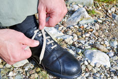 Tying the shoes. A man tying shoelaces and getting ready for walking in the park Stock Image