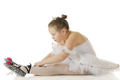Tying on Slippers. An elemantary ballerina tying on her zebra-stripped slippers while in her dance costume.  On a white background Stock Photography
