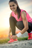 Tying sport shoe. Smiling woman tying her sport shoe Royalty Free Stock Photography