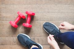 Tying sport shoes, Asian woman getting ready for weight training. Exercise, Fitness training. Healthy lifestyle. Concept royalty free stock photo