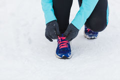 Tying sport shoes in snow. Winter sports fashion concept. Tying sport fitness shoes in snow, footwear for workout outside Stock Images