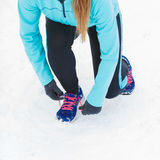 Tying sport shoes in snow. Winter sports fashion concept. Tying sport fitness shoes in snow, footwear for workout outside Royalty Free Stock Photos