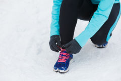 Tying sport shoes in snow. Winter sports fashion concept. Tying sport fitness shoes in snow, footwear for workout outside Stock Photo