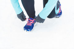 Tying sport shoes in snow. Winter sports fashion concept. Tying sport fitness shoes in snow, footwear for workout outside Stock Photography