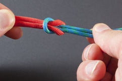 Tying a Square Knot. A square knot used to tie two paracords together Royalty Free Stock Images