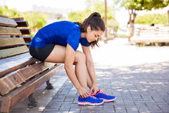 Tying tennis shoes in a park. Profile view of a young woman tying her shoes in the park before going for a run stock photo