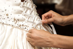 Tying up. Someone lacing up the brides wedding dress royalty free stock images