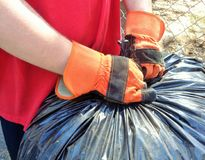 Tying Up Yard Bags 2. This is an image of a man tying up yard bags while doing yard clean up. He is wearing two orange and black, cloth and leather work gloves royalty free stock photos