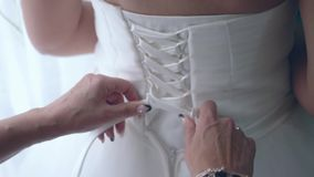 Tying the wedding dress stock video