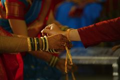 Tying wedding knot on hand of groom. Hindu marriage ritual Stock Photo