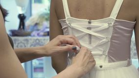 Tying a white corset on beautiful dress. Tying a white corset on a beautiful dress. The woman puts the lace into of the rings on dress and tying a white bow stock video