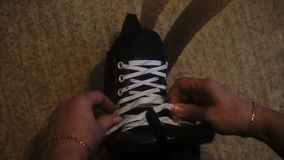 Tying the white laces on skates,preparing to go on the ice.  stock footage