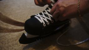 Tying the white laces on skates,preparing to go on the ice.  stock video