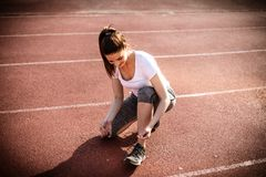 Tying your shoe good before go to run. Young woman. Stock Photos