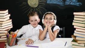 tylna koncepcji do szkoły Chłopiec i dziewczyna siedzimy przy biurkiem z rozsypiskami książki i blackboard z dzieciaków rysunkami zbiory
