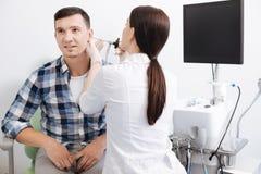 Tylna strona młodej kobiety lekarki wzruszający męski ucho Obraz Royalty Free