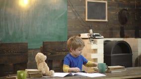 tylna szko?y Szcz??liwy u?miechni?ty ucznia rysunek przy biurkiem Dziecko w klasowym pokoju z blackboard na tle teddy zdjęcie wideo
