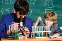 tylna szko?y uczeń robi nauce eksperymentuje z mikroskopem w lab ojciec i syn przy szkołą nauczyciela mężczyzna z obraz stock