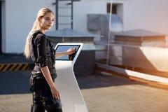 Tylna widok fotografia przyjemny kobiety dosunięcie na ekranie na EMS maszynie fotografia stock
