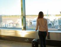 Tylna widok młoda kobieta z walizką w nowożytny lotniskowy śmiertelnie fotografia royalty free