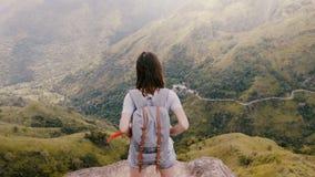 Tylna wysokiego kąta widoku szczęśliwa turystyczna kobieta z plecaka wzruszającym włosy przy oszałamiająco halnym sceneria widoki zbiory