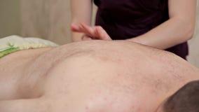 tylne masa? Dziewczyna masażysta w purpurowym kostiumu robi relaksującemu masażowi zdjęcie wideo