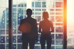 Tylne widok sylwetki dwa partnera biznesowego patrzeje zamyślenie z biurowego okno fotografia royalty free