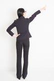 Tylnego widoku Azjatycki bizneswoman wskazuje daleko od zdjęcie royalty free
