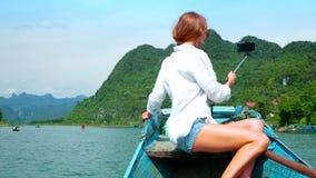 Tylnego widoku blond kobieta robi selfie żeglowaniu na rzecznej łodzi zbiory wideo