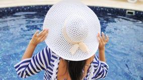 Tylnego widoku kobiety ładny obsiadanie na krawędzi pływacki basen ma zabawę i cieszy się wakacje zdjęcie wideo