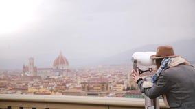Tylnego widoku szczęśliwy młody żeński podróżnik używa monetę działał teleskop przy zadziwiającą miasto panoramą jesień Florencja zdjęcie wideo