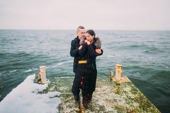 Tylni romantyczny widok młoda para pozuje na drylującym molu podczas dżdżystego jesień dnia Zimy morza tło fotografia stock