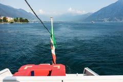 Tylni widok łódź na lago maggiore z flaga, błękitne wody i widok górski Zdjęcia Royalty Free