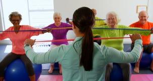 Tylni widok żeńskiego trenera stażowi starszy ludzie w ćwiczeniu przy sprawności fizycznej studiiem 4k zdjęcie wideo