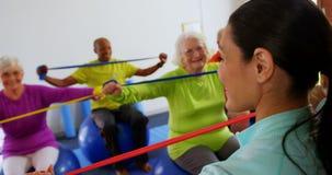 Tylni widok żeńskiego trenera stażowi starszy ludzie w ćwiczeniu przy sprawności fizycznej studiiem 4k zbiory
